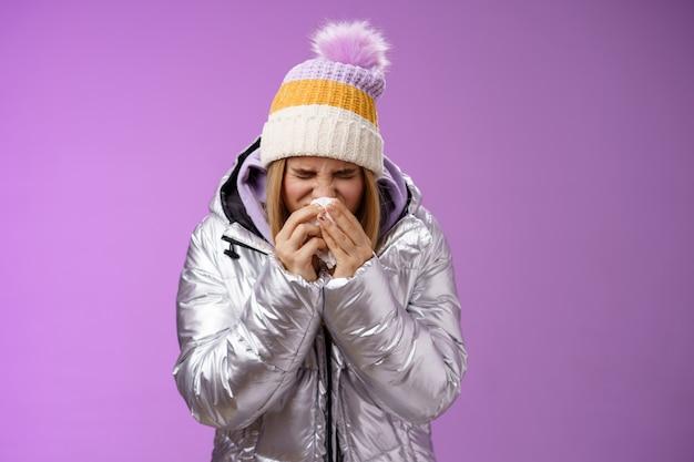 Девушка насморк чихает ткань пресс салфетку лицо заболела, плохо себя чувствует, больна возглавляет больницу, стоя на фиолетовом фоне, изгибаясь в серебряной стильной куртке, зимней шапке, плачет, рыдая.