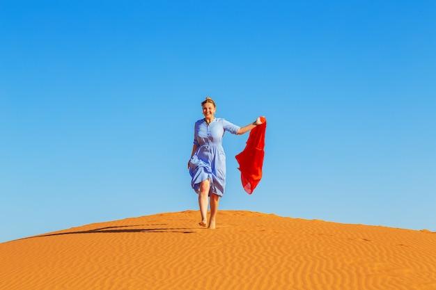 Girl runs along the sahara desert.