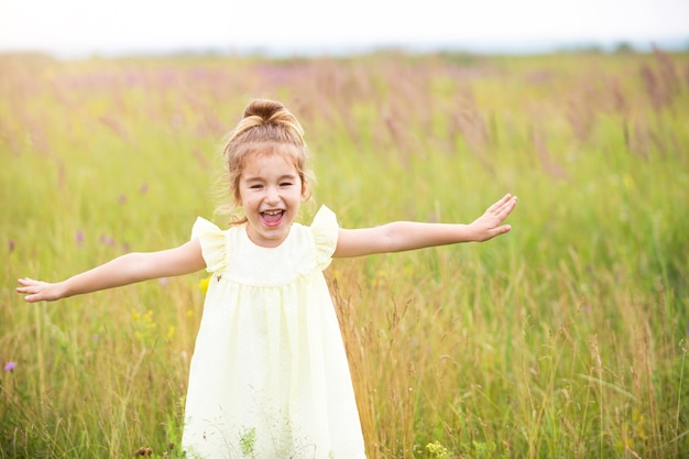 The girl runs into the field with her arms outstretched like an airplane. carefree childhood, summer freedom, travel. international children day. mosquito repellent, cottage core.