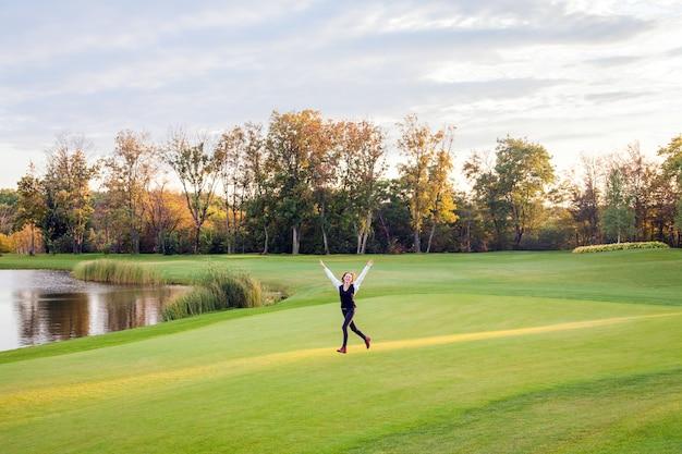 女の子はゴルフコースの緑の芝生の上を走ります。女の子の幸せ。アウトドアショット Premium写真