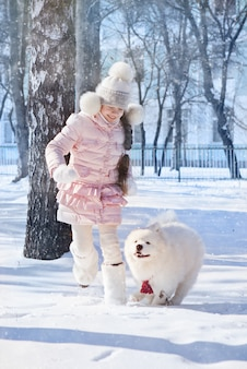 A girl runs and plays with a samoyed dog in the snow,