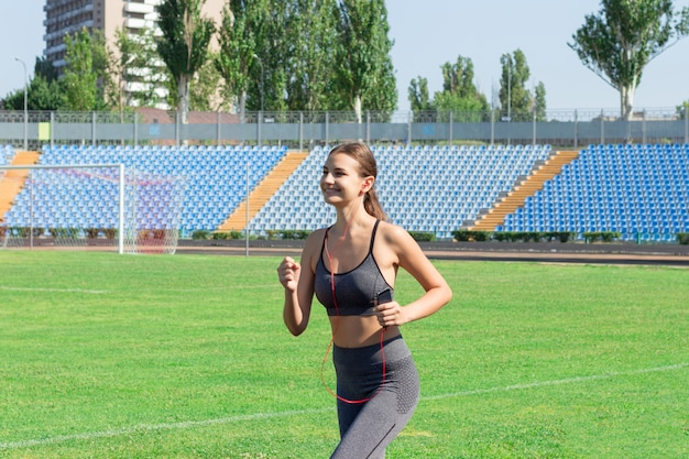 Girl runs in the stadium and listening music to the player. sports and healthy concept