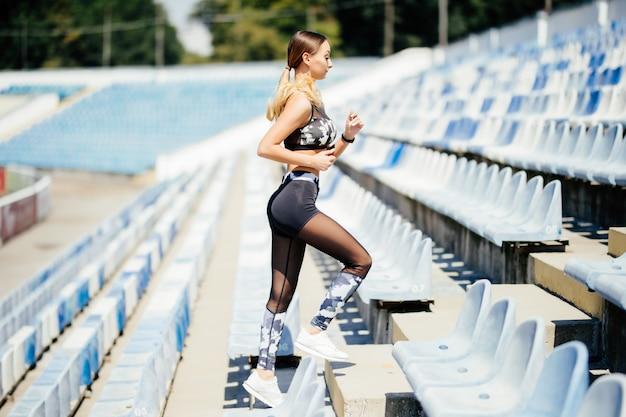 여자는 위층 일몰으로 실행합니다. 경기장에 운동복 훈련에서 젊은 여자. 공간을 복사하십시오. 도시 개념의 건강한 라이프 스타일