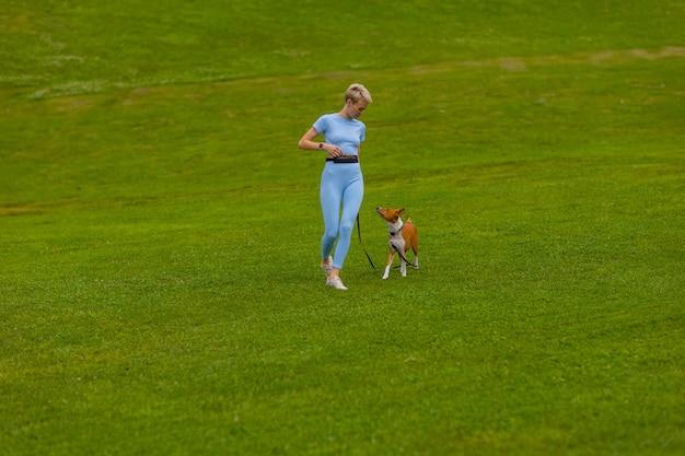 소녀는 해질녘 잔디밭에 있는 공원에서 개와 함께 뛰고, 자연 속에서 애완동물을 산책시킵니다.