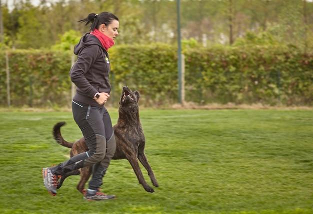 女の子は公園で犬と一緒に走る