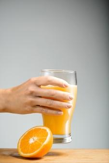 Braccio della ragazza che tiene vetro di succo d'arancia