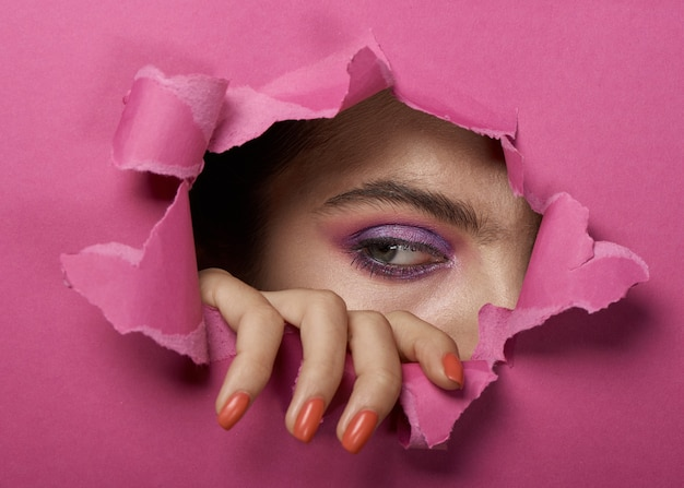 Girl's eye with makeup in a torn pink paper hole.