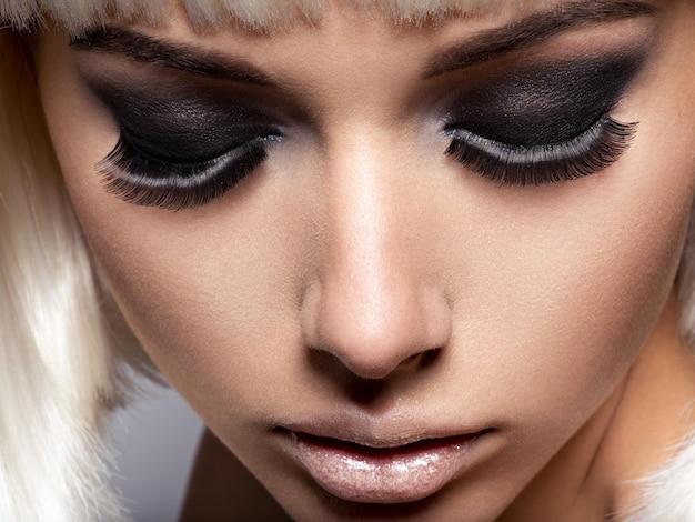 Primo piano del viso della ragazza con lunghe ciglia nere. trucco di moda