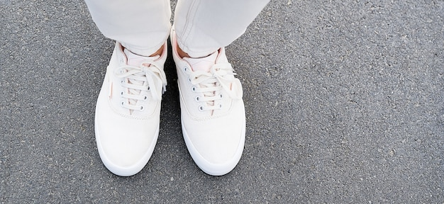 The girl's feet in white jeans and sneakers on the sidewalk.