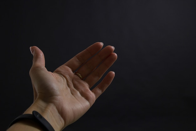 Girl's hand on a black background stretched forward inviting or showing somewhere. copy space