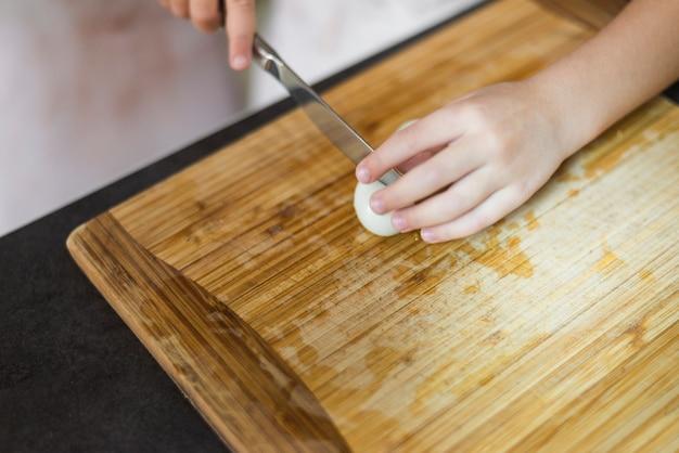 여자의 손을 커팅 보드에 칼으로 삶은 계란을 절단