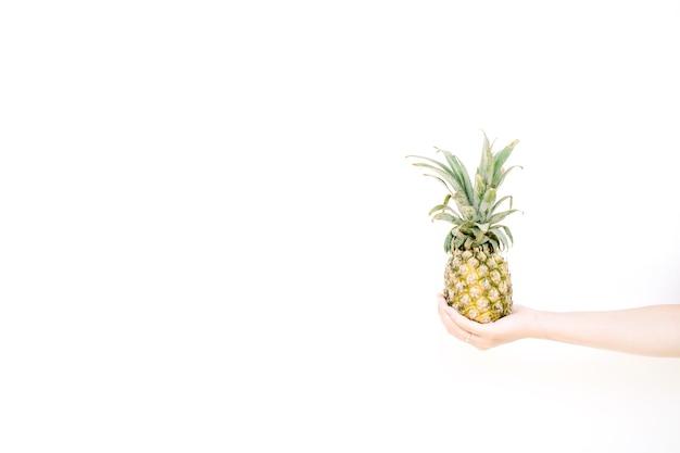 パイナップルを持っている女の子の手。