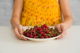 Girl's hand holding red cherries on plate over the white desk
