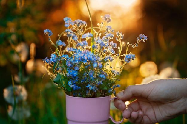 소녀의 손은 봄 정원에서 물망초 꽃 꽃다발과 함께 컵을 들고 있습니다.