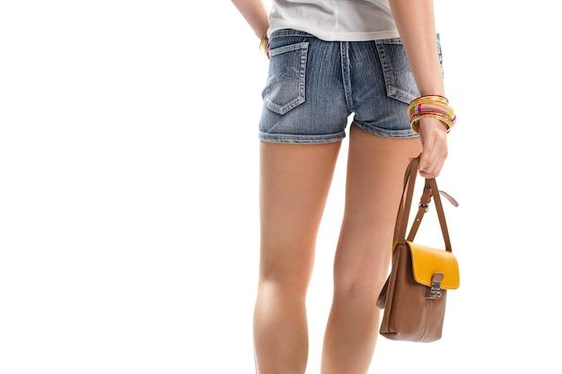 소녀의 손에는 가방이 있습니다. 파란색의 짧은 반바지. 가죽 핸드백과 데님 반바지. 여름에 어울리는 매력적인 옷.