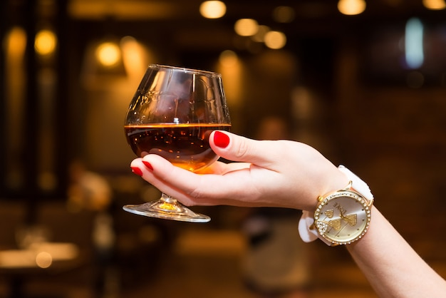 The girl's hand holds a glass of cognac