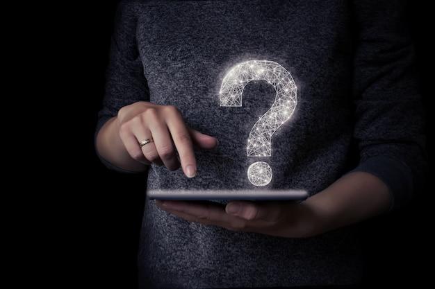 女の子の手は、仮想ホログラムの疑問符が付いたタブレットを持っています。