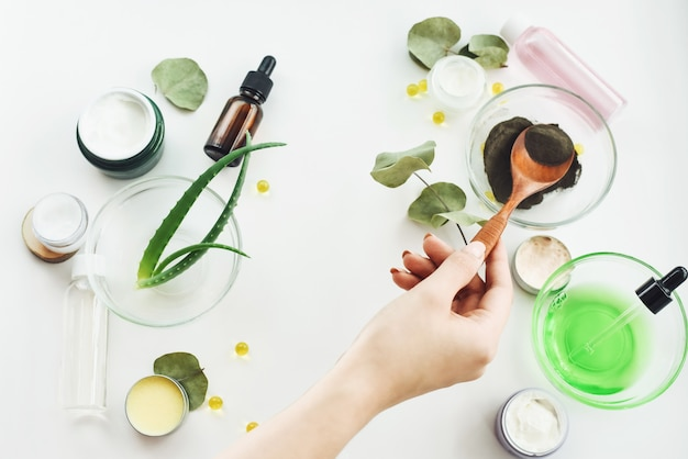 A girl's hand mixes the ingredients to create a moisturizing serum. natural ingredients on a white table. black clay, aloe vera leaves, moisturizing cream, balm and tonics