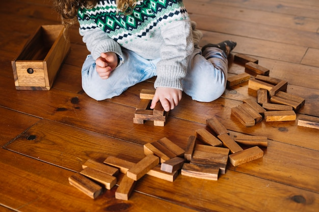 Girl's hand playing wooden block game at home