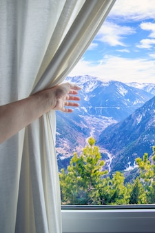 Girl's hand pulling back the curtain to see the mountains in the window.
