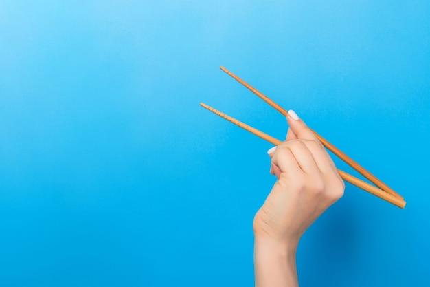 Рука девушки показывает палочки для еды на синей поверхности.