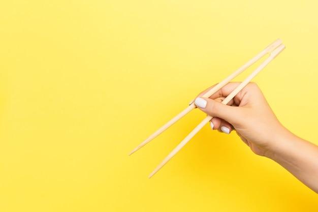 Рука девушки показывает палочки для еды на желтой поверхности.