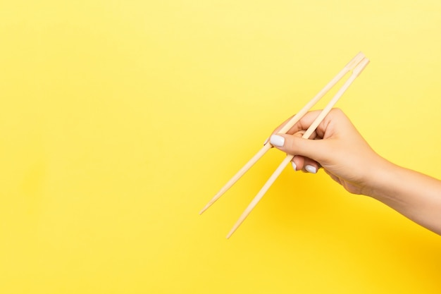 Girl's hand showing chopsticks on yellow . asian cuisine  with empty