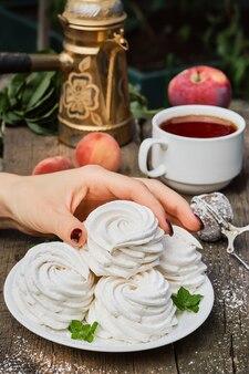 Рука девушки берет зефир (зефир) с белой тарелки, чашку чая и фрукты на винтажном столе, крупный план, послеобеденный чай в саду. воздушные русские сладости