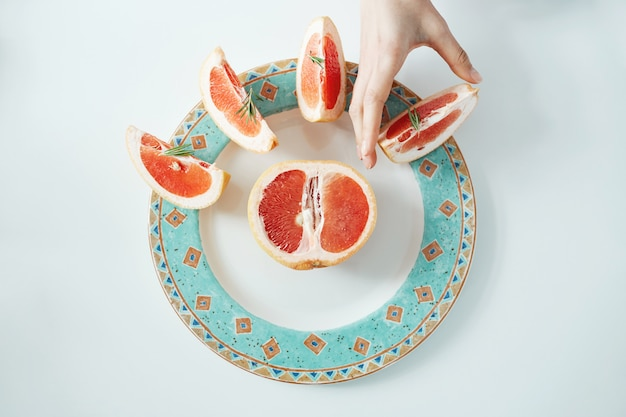 Girl's hand taking slice of grapefruit from white plate. from above. healthy diet nutrition.