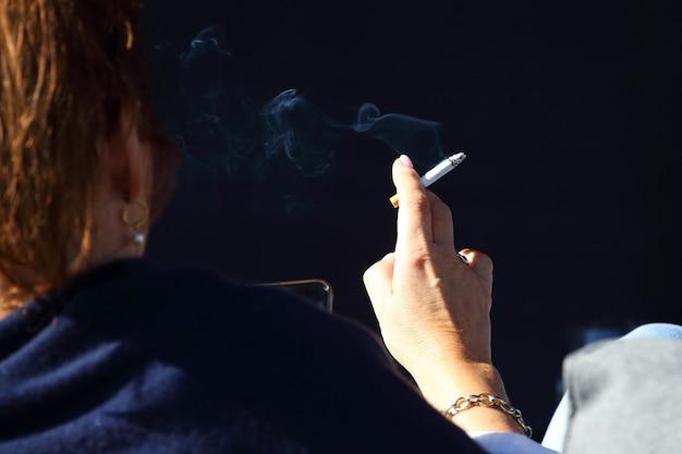 スマートフォンとタバコを持った少女の手