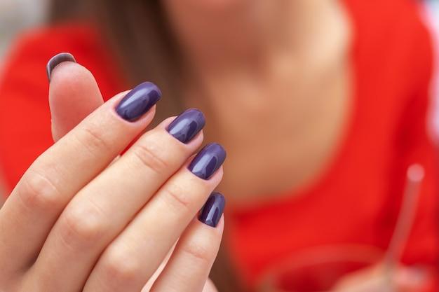 빨간 드레스 배경에 짙은 보라색 손톱이 있는 소녀의 손
