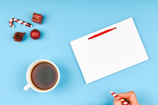 Рука девушки пишет новогодние пожелания. девушка пишет ручкой на листе бумаги рождественские пожелания.