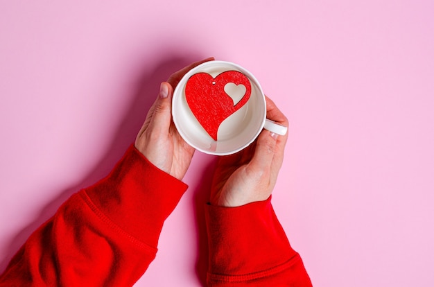 The girl's hands are holding a white cup with a wooden red heart inside on pink