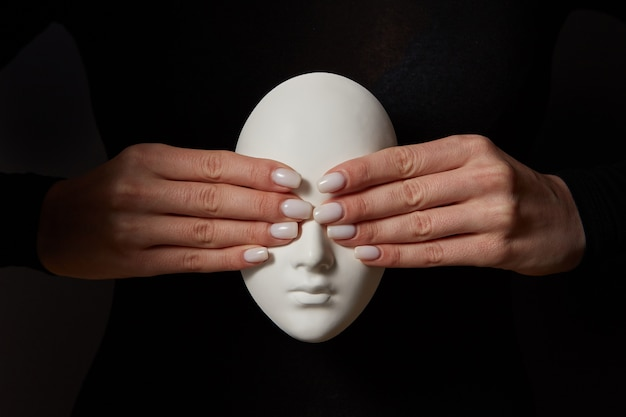Girl's hands close eyes of plaster mask face on a black wall. see no evil. concept three wise monkeys. place for text.