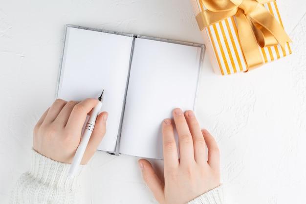 Руки девушки держат пустой блокнот среди подарочной коробки. цели, планы, мечты, список дел