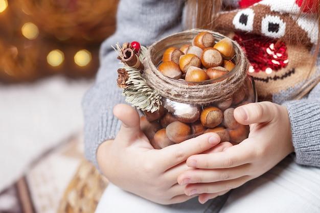 ナッツの銀行を保持している女の子の手。クリスマスと新年のコンセプト。ボケ味と日光とお祭りの背景。魔法のおとぎ話