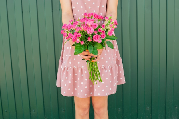 Girl's hands holding beautiful bouquet of pink roses