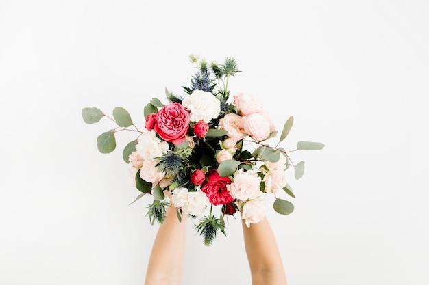 美しい花の花束を持っている女の子の手:大げさなバラ、青いエリンギウム、ユーカリ、白で隔離