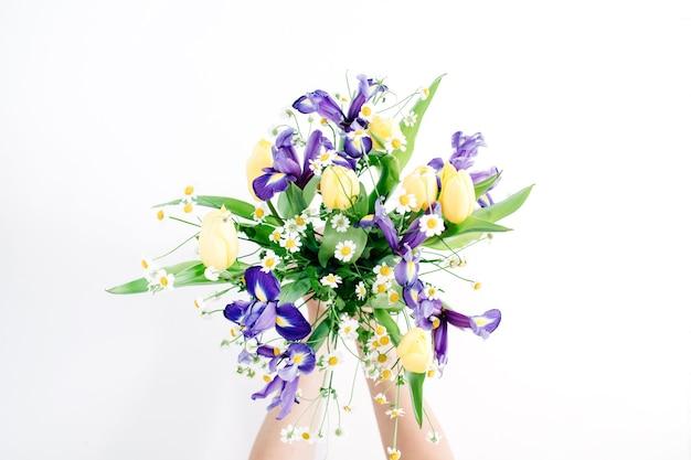 美しい花の花束を持つ少女の手: 白い背景にチューリップ、カモミール、アイリスの花。フラット レイアウト、トップ ビュー。フラワーアレンジメント
