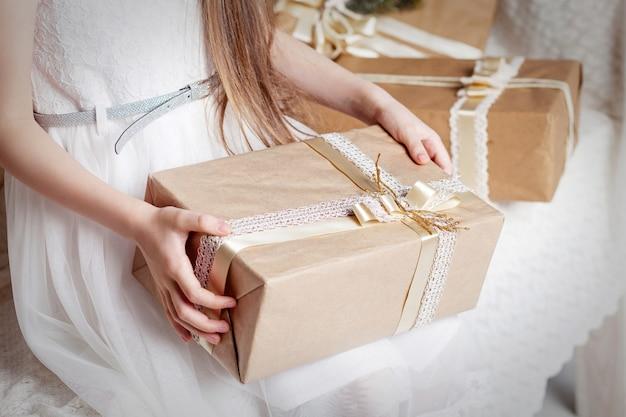 ギフトボックスを保持している女の子の手。スペースをコピーします。クリスマス、ヒューイヤー、誕生日のコンセプト。