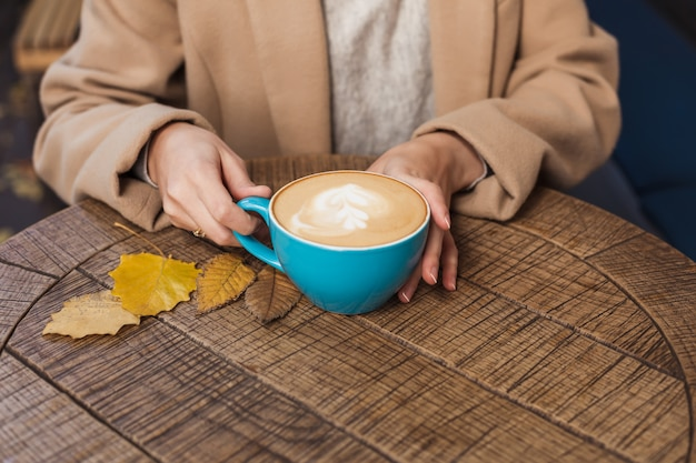 Girl's hands holding a hot cup of coffee close-up. autumn