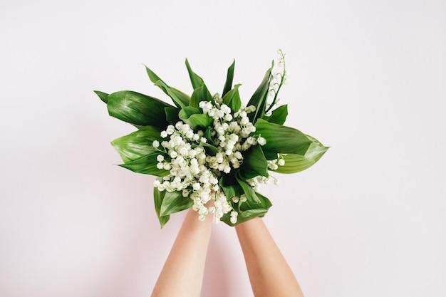 핑크에 흰색 은방울꽃 꽃다발을 들고 여자의 손