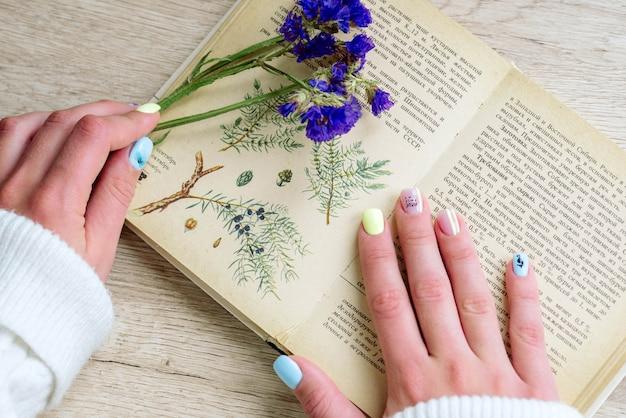 花と本の女の子の手。