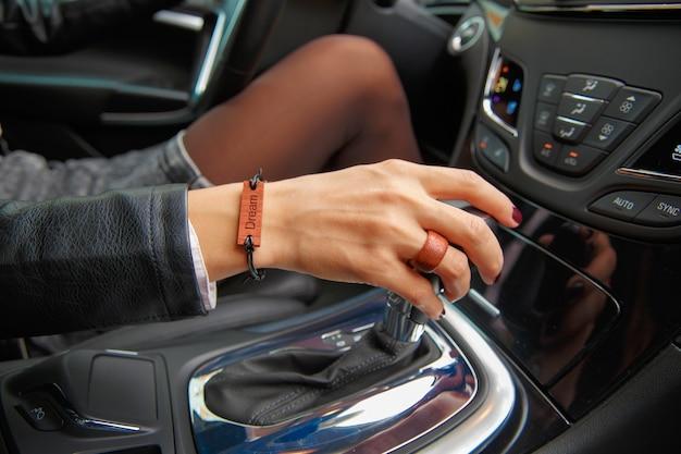 자동차의 스티어링 휠에 소녀의 손, 그녀의 손에 비문 꿈이있는 팔찌