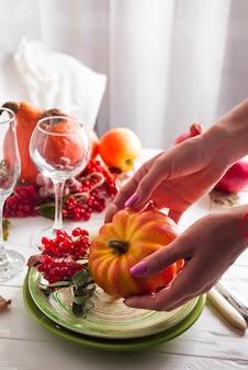 Girl's hands prepare thanksgiving festive table setting