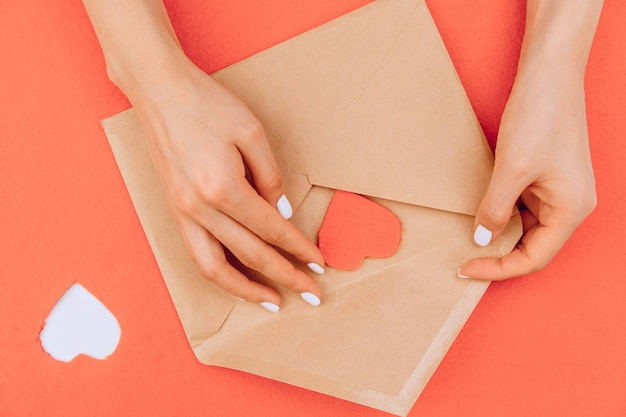The girl's hands put a heart cut out on the background in an envelope. valentine card. valentine's day concept. flat lay.