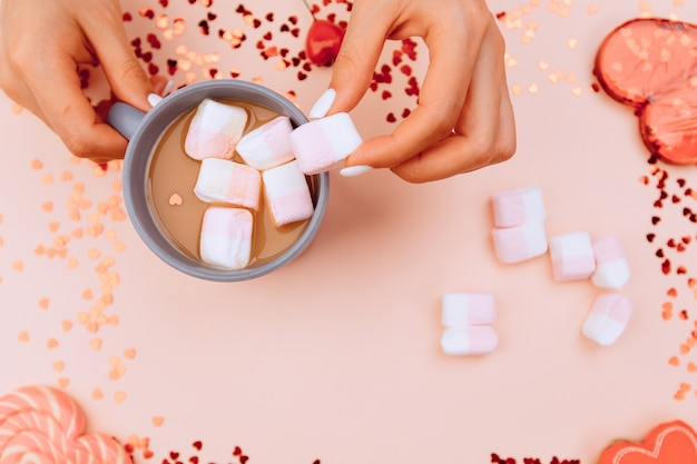 Girl's hands put marshmallows in a cup of coffee and on trendy pink paper. valentine's day and womens day concept. top view