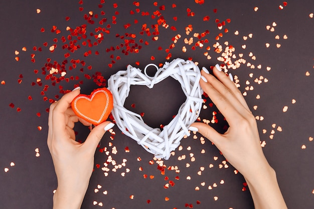 The girl's hands puts a small red heart with a large white wicker heart. small hearts are scattered around. love concept. st. valentine's day
