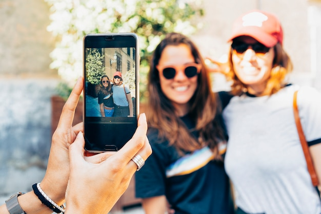 Girl's hands taking photo with a smartphone of a happy women lesbian couple in madrid.