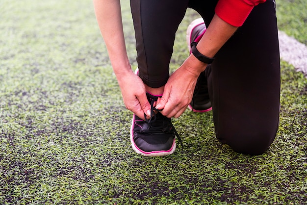 Girl's hands tie shoelace on sports shoes at the sports stadium
